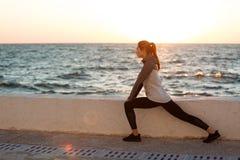 Giovane donna adatta che fa allungando allenamento alla spiaggia Fotografia Stock