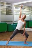 Giovane donna adatta che fa allungando esercizio in palestra Immagini Stock Libere da Diritti