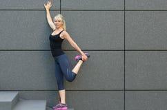Giovane donna adatta che fa allungando gli esercizi in città Fotografie Stock Libere da Diritti