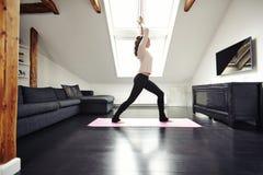 Giovane donna adatta che fa yoga a casa Immagini Stock