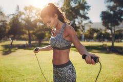 Giovane donna adatta con la corda di salto in un parco Fotografia Stock Libera da Diritti