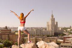 Giovane donna adatta con le mani sollevate sopra la città fotografie stock libere da diritti