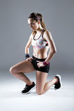 Giovane donna adatta e sportiva che prepara per un funzionamento sul backgrou bianco Fotografia Stock
