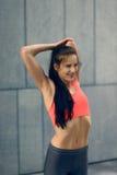 Giovane donna adatta sorridente che fa allungando gli esercizi Immagine Stock