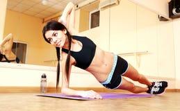Giovane donna adatta sorridente che fa gli esercizi di forma fisica Fotografia Stock