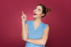 Giovane donna adorabile felice che sta e che indica su Fotografie Stock
