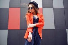 Giovane donna adorabile sveglia in occhiali da sole, rivestimento rosso, cappello di modo, controllante fondo astratto all'aperto immagini stock