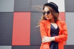 Giovane donna adorabile sveglia in occhiali da sole, rivestimento rosso, cappello di modo, controllante fondo astratto all'aperto immagine stock libera da diritti
