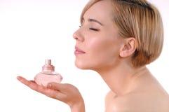 Giovane donna adulta che gode dell'odore di un profumo fiorito Fotografia Stock Libera da Diritti