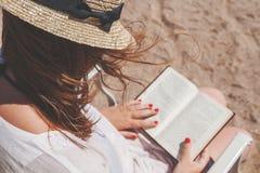 Giovane donna adulta con un cappello sulla spiaggia che legge un libro immagini stock