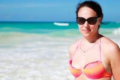Giovane donna adulta sorridente sulla spiaggia fotografia stock