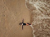 Giovane donna aerea di vista superiore che si trova sulla spiaggia di sabbia e sulle onde fotografia stock libera da diritti