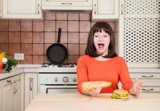 Giovane donna affamata divertente con la bocca aperta che mangia gli alimenti a rapida preparazione i del ciarpame fotografia stock