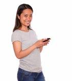 Giovane donna affascinante asiatica che per mezzo del suo cellulare Fotografia Stock