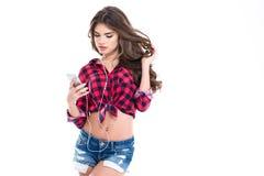 Giovane donna affascinante attraente che ascolta la musica facendo uso del telefono cellulare immagine stock