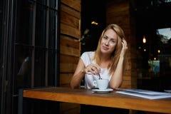 Giovane donna affascinante che posa mentre sedendosi in caffè durante la pausa caffè, resto godente femminile europeo attraente d Fotografia Stock