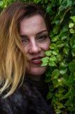 Giovane donna affascinante con capelli lunghi che stanno vicino alla parete con le foglie decorative del giorno selvaggio di autu Immagine Stock Libera da Diritti