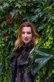 Giovane donna affascinante con capelli lunghi che stanno vicino alla parete con le foglie decorative del giorno selvaggio di autu Immagini Stock