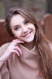 Giovane donna affascinante con capelli marroni lunghi in un cappotto beige fotografia stock