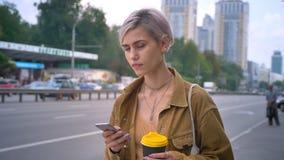 Giovane donna affascinante con il breve caffè e telefono rosa della tenuta di taglio di capelli, bus aspettante o taxi, stante su archivi video