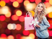 Giovane donna affascinante con il sacchetto della spesa ed il regalo fotografia stock