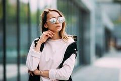 Giovane donna affascinante nel distogliere lo sguardo alla moda degli occhiali da sole Immagine Stock