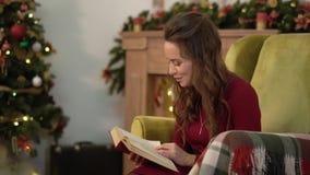 Giovane donna affascinante sveglia che legge un libro che si siede in una sedia accanto all'albero di Natale archivi video