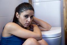 Giovane donna affetta da bulimia triste e depressa che ritiene seduta malata al pavimento della toilette che si appoggia WC Fotografia Stock Libera da Diritti