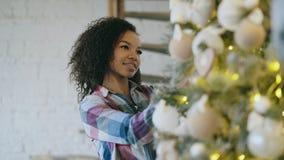 Giovane donna africana attraente che decora l'albero di Natale a casa che prepara per la celebrazione di natale Immagini Stock Libere da Diritti