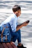 Giovane donna africana attraente che si siede sul banco fuori con il telefono cellulare Immagine Stock Libera da Diritti