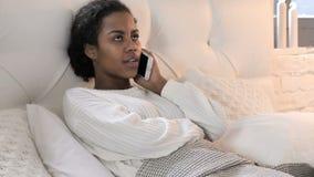 Giovane donna africana che parla sul telefono mentre rilassandosi a letto video d archivio