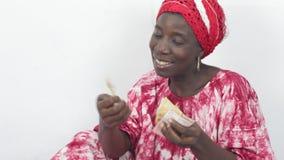 Giovane donna africana che si siede e che conta i suoi soldi video d archivio