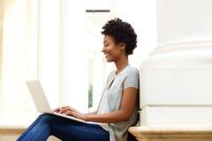 Giovane donna africana che si siede fuori facendo uso del computer portatile Fotografie Stock