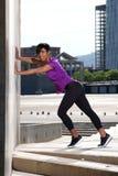 Giovane donna africana integrale che fa allungando allenamento all'aperto Fotografie Stock Libere da Diritti