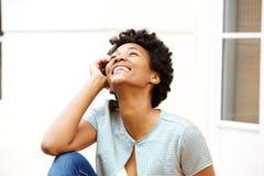 Giovane donna africana sorridente che si siede all'aperto e cercare Immagine Stock