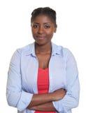 Giovane donna africana sorridente con le armi attraversate Immagini Stock