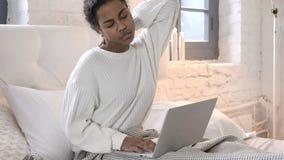 Giovane donna africana stanca con funzionamento di dolore al collo sul computer portatile a letto stock footage