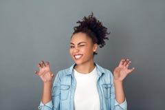 Giovane donna africana sulla posa quotidiana casuale del gatto di stile di vita dello studio grigio della parete Immagine Stock