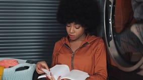 Giovane donna afroamericana attraente che legge un libro mentre lavando la sua lavanderia alla lavanderia automatica video d archivio