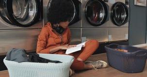 Giovane donna afroamericana attraente che legge un libro mentre lavando la sua lavanderia alla lavanderia automatica stock footage