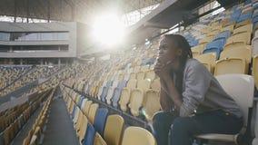 Giovane donna afroamericana attraente premurosa che si siede sulla sedia gialla dello stadio allo stadio vuoto stock footage