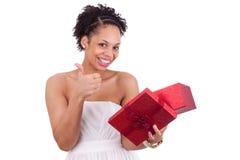 Giovane donna afroamericana che apre un contenitore di regalo Fotografie Stock