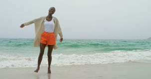 Giovane donna afroamericana che balla sulla spiaggia 4k archivi video