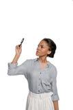Giovane donna afroamericana che esamina lente isolata su bianco Fotografia Stock