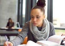 Giovane donna afroamericana che fa le assegnazioni in biblioteca Immagine Stock Libera da Diritti