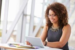 Giovane donna afroamericana che lavora con la compressa in ufficio Fotografia Stock Libera da Diritti