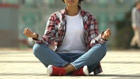 Giovane donna afroamericana che medita yoga nella posizione di loto sulla via urbana occupata archivi video