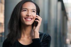 Giovane donna afroamericana che parla sul telefono Fotografia Stock