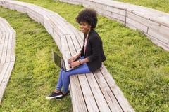 Giovane donna afroamericana che per mezzo del computer portatile Ambiti di provenienza verdi casua Fotografie Stock