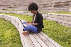 Giovane donna afroamericana che per mezzo del computer portatile Ambiti di provenienza verdi casua Fotografia Stock